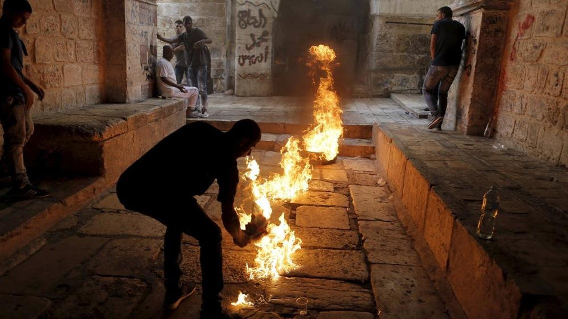 A Palestinian protester kicks a burning tyre during clashes between Palestinians and Israeli police officers in Jerusalem's Old City, September 15, 2015. The U.S. State Department on Monday voiced concern about violence at the compound surrounding Jerusalem's Al-Aqsa mosque, an area revered by Muslims as the Noble Sanctuary and by Jews as the Temple Mount. REUTERS/Ammar Awad TPX