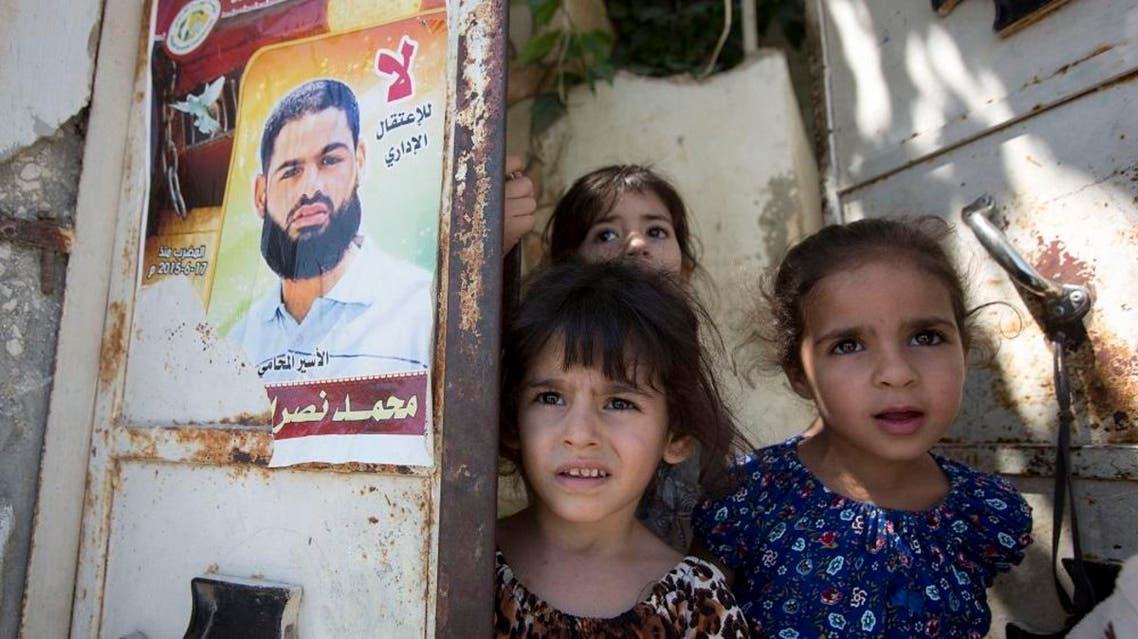 Palestinian girls stand next to a poster showing their uncle Mohammed Allan at their family house in the village of Einabus. (AP)