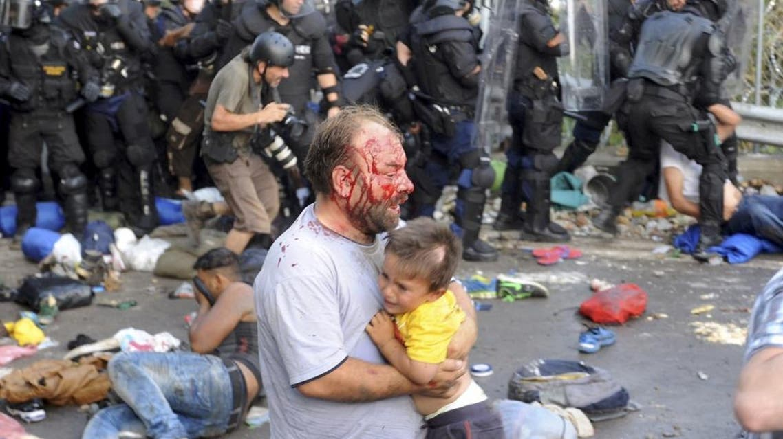 An injured migrant carries a child during clashes with Hungarian riot police at the border crossing with Serbia in Roszke, Hungary September 16, 2015. REUTERS