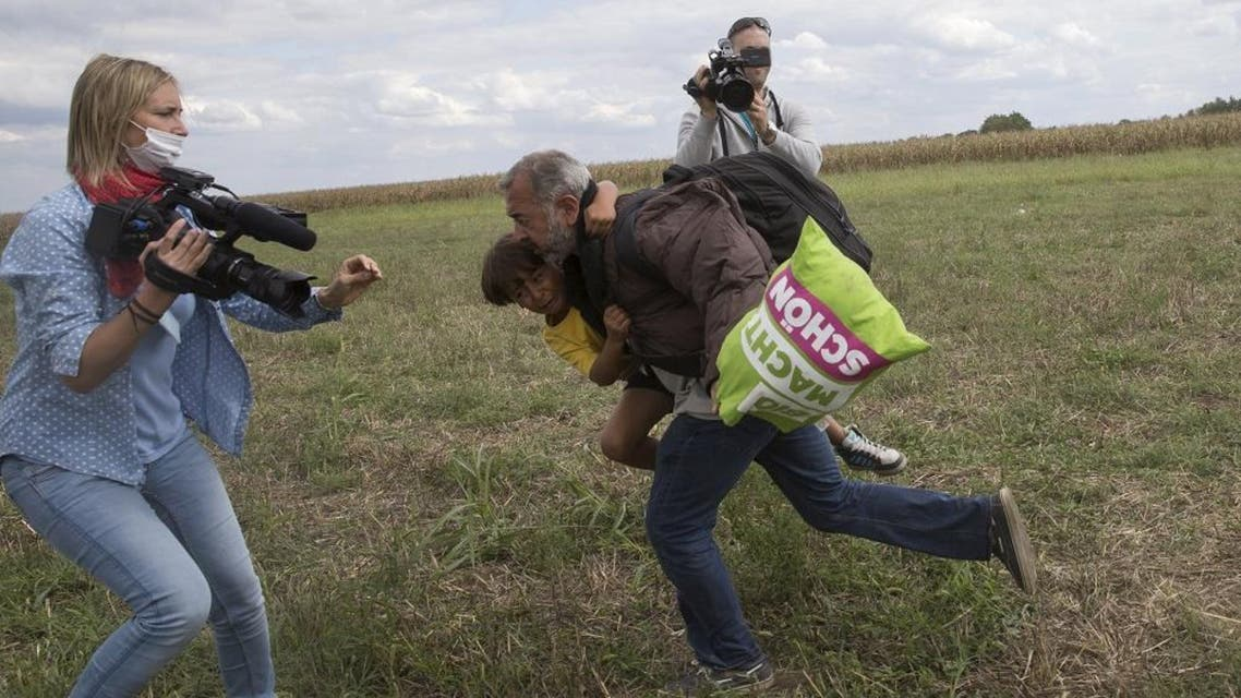 A migrant runs with a child before tripping on TV camerawoman Petra Laszlo (L) and falling as he tries to escape from a collection point in Roszke village, Hungary, September 8, 2015. Laszlo, a camerawoman for a private television channel in Hungary, was fired late on Tuesday after videos of her kicking and tripping up migrants fleeing police, including a man carrying a child, spread in the media and on the internet. REUTERS/Marko Djurica