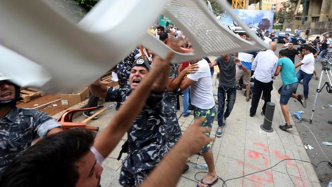 A thrown chair flies over Lebanese policemen as they push back supporters of Lebanese Parliament Speaker Nabih Berri during clashes with anti-government protesters in downtown Beirut, Lebanon, Wednesday, Sept. 16, 2015. Lebanese police beat back protesters in downtown Beirut Wednesday ahead of the second session of dialogue between senior politicians, amid widespread anger over the government's failure to deal with the country's trash crisis and other political problems. (AP Photo/Bilal Hussein)