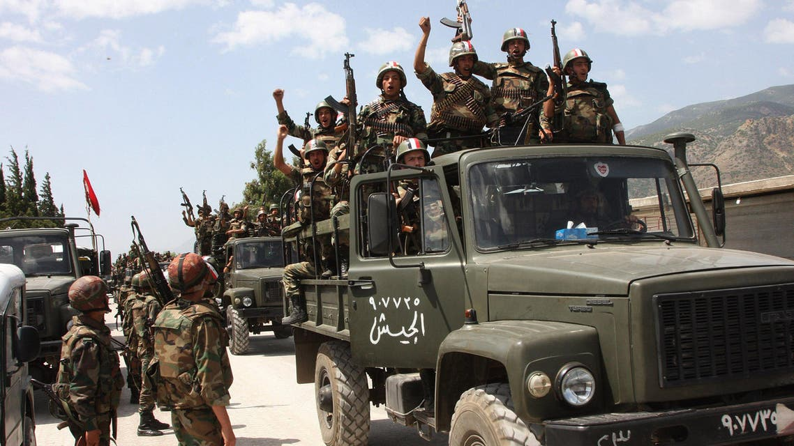 n this June 10, 2011, file photo, taken during a government-organised visit for media, Syrian army soldiers standing on their military trucks shout slogans in support of Syrian President Bashar Assad