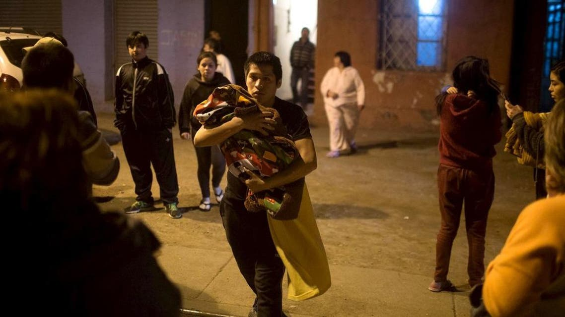 Residents wait on a street outside their houses after an earthquake hit Chile's central zone, in Santiago