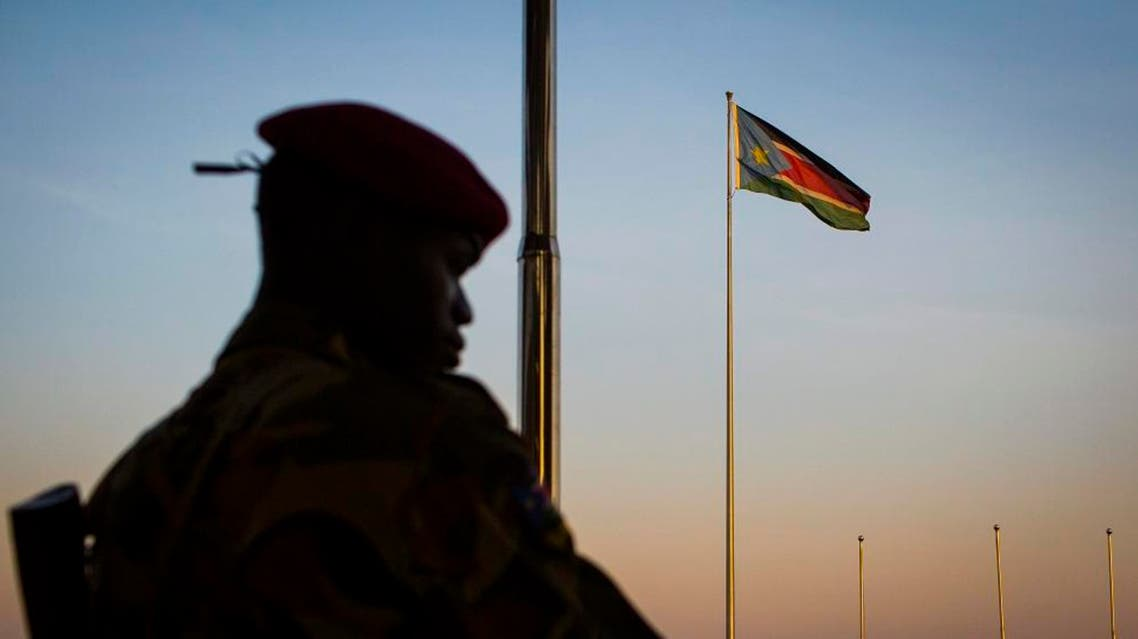A South-Sudanese government soldier stands guard as a South Sudanese flag flies in the background AP