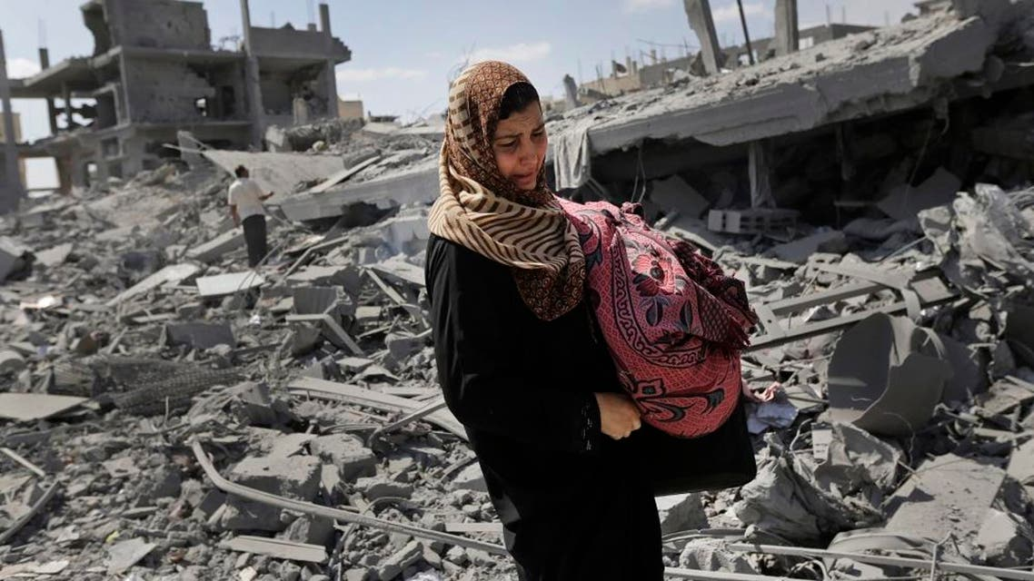 A Palestinian woman carries her belongings past the rubble of houses destroyed by Israeli strikes in Beit Hanoun, northern Gaza Strip, Saturday, July 26, 2014. AP