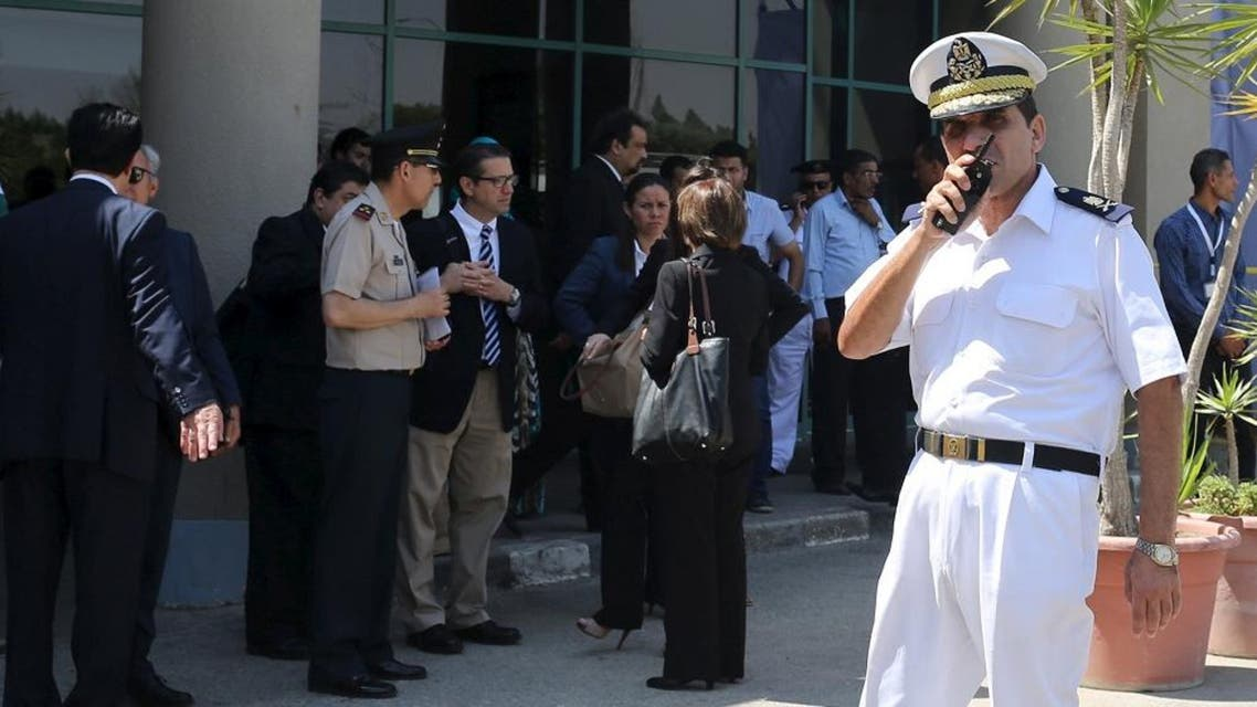 Egyptian police officer uses a walkie-talkie as Mexican embassy members stand outside Dar Al Fouad Hospital in Cairo. (Reuters)