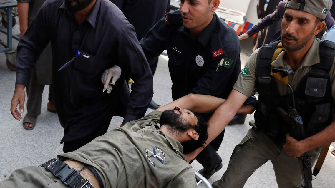 Pakistani security officials rush their colleague to a local hospital, Friday, Sept. 18, 2015 in Peshawar, Pakistan after the Taliban launched a brazen assault on a military base on the outskirts of the northwestern city, storming a mosque inside the sprawling compound and killing many worshippers during prayers. (AP Photo/Mohammad Sajjad)