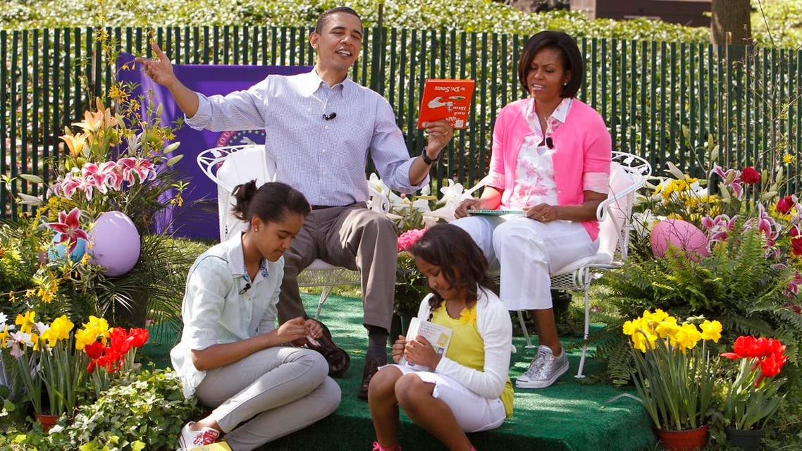 """President Barack Obama holds """"Green Eggs and Ham"""" by Dr. Seuss as he hosted the annual White House Easter Egg Roll, Monday, April 5, 2010, on the South Lawn of the White House in Washington."""