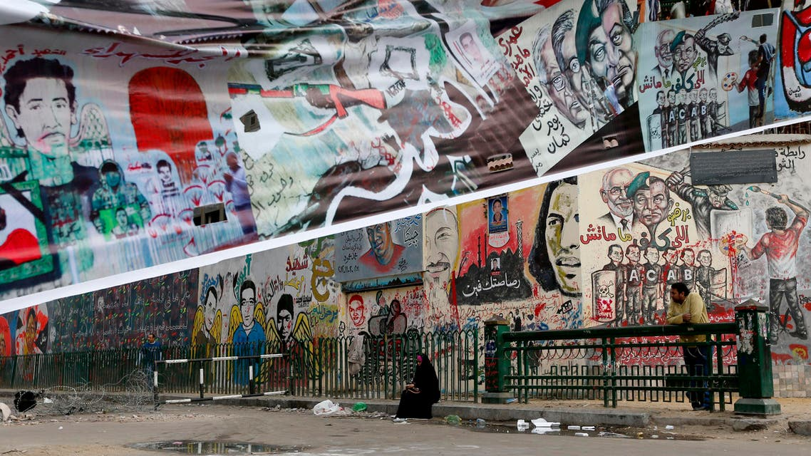 A woman sits near graffiti painted on a wall near Tahrir Square in Cairo, Egypt, Friday, Dec. 14, 2012. Opposing sides in Egypt's political crisis were staging rival rallies on Friday, the final day before voting starts on a contentious draft constitution that has plunged the country into turmoil and deeply divided the nation.(AP Photo/Petr David Josek)