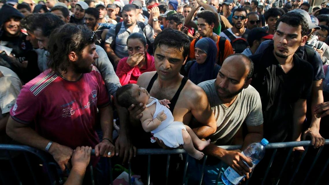 A migrant holds a baby as he waits to board a bus in Tovarnik, Croatia, September 17, 2015. reuters