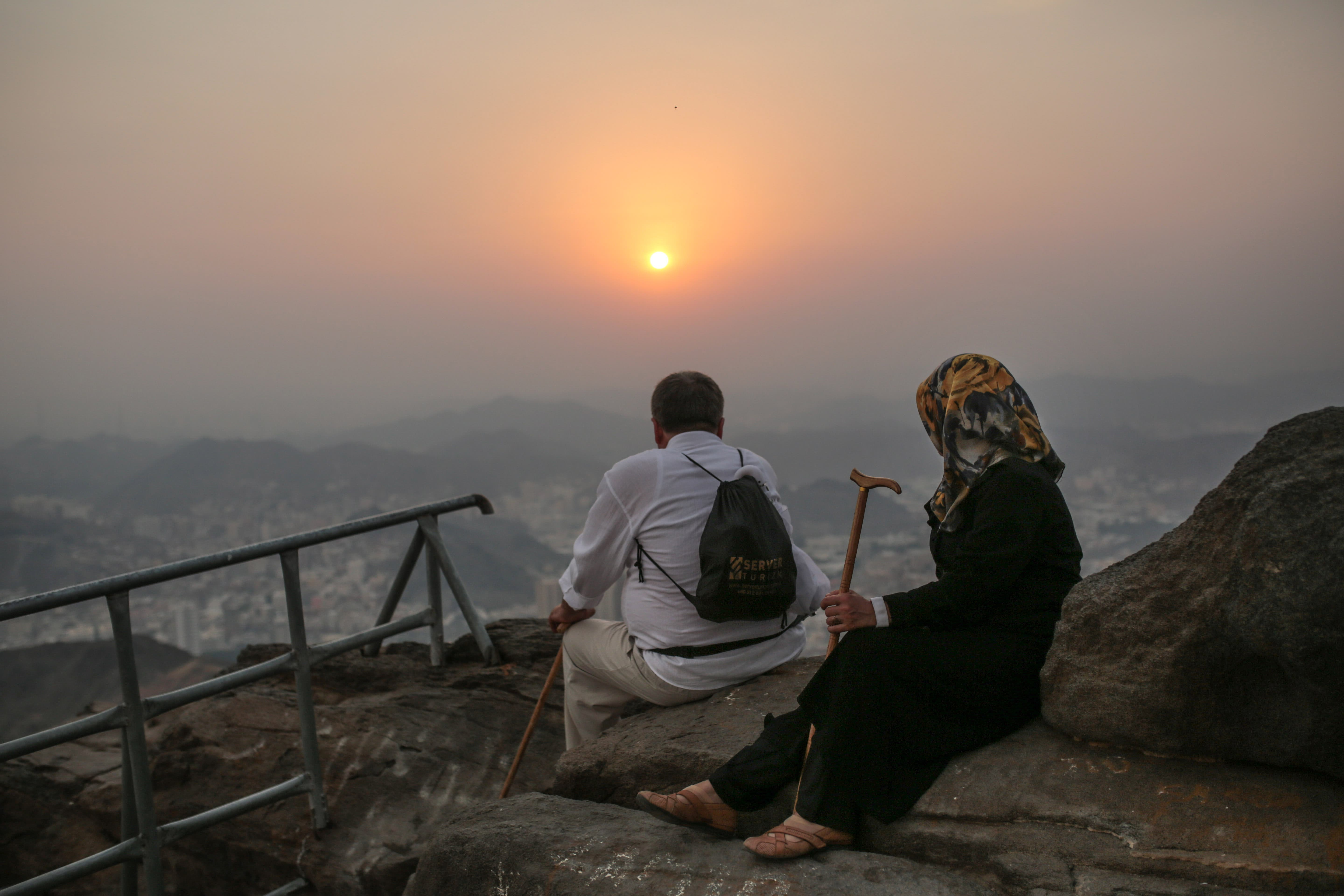 Muslim pilgrims observe sunset from atop Noor Mountain next to Hiraa cave, where Prophet Muhammad received his first revelation from God to preach Islam, on the outskirts of Mecca, Saudi Arabia, Friday, Sept. 18, 2015. (AP)