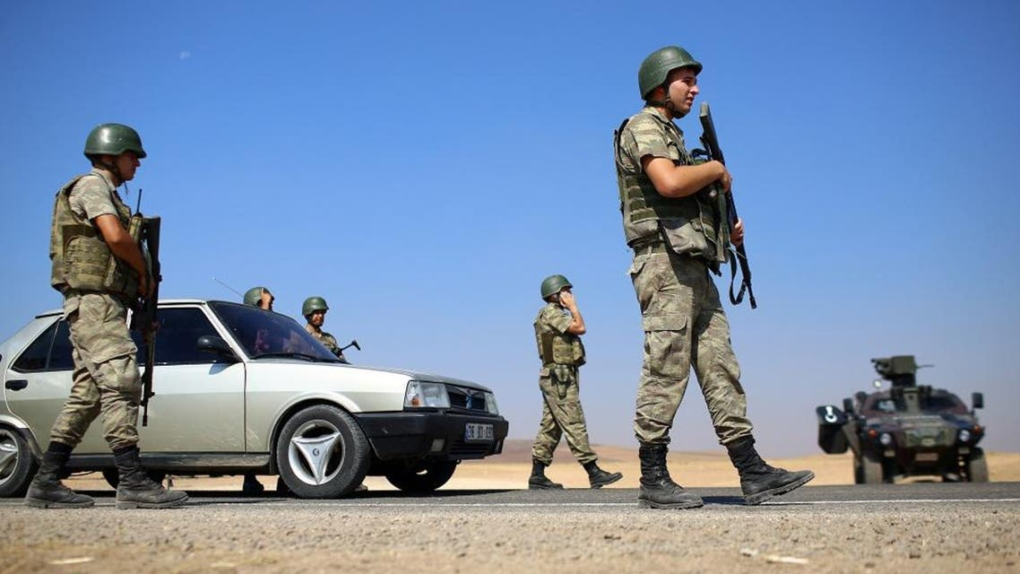 Turkish soldiers take position on a road near Suruc on the border with Syria. (AP Photos)