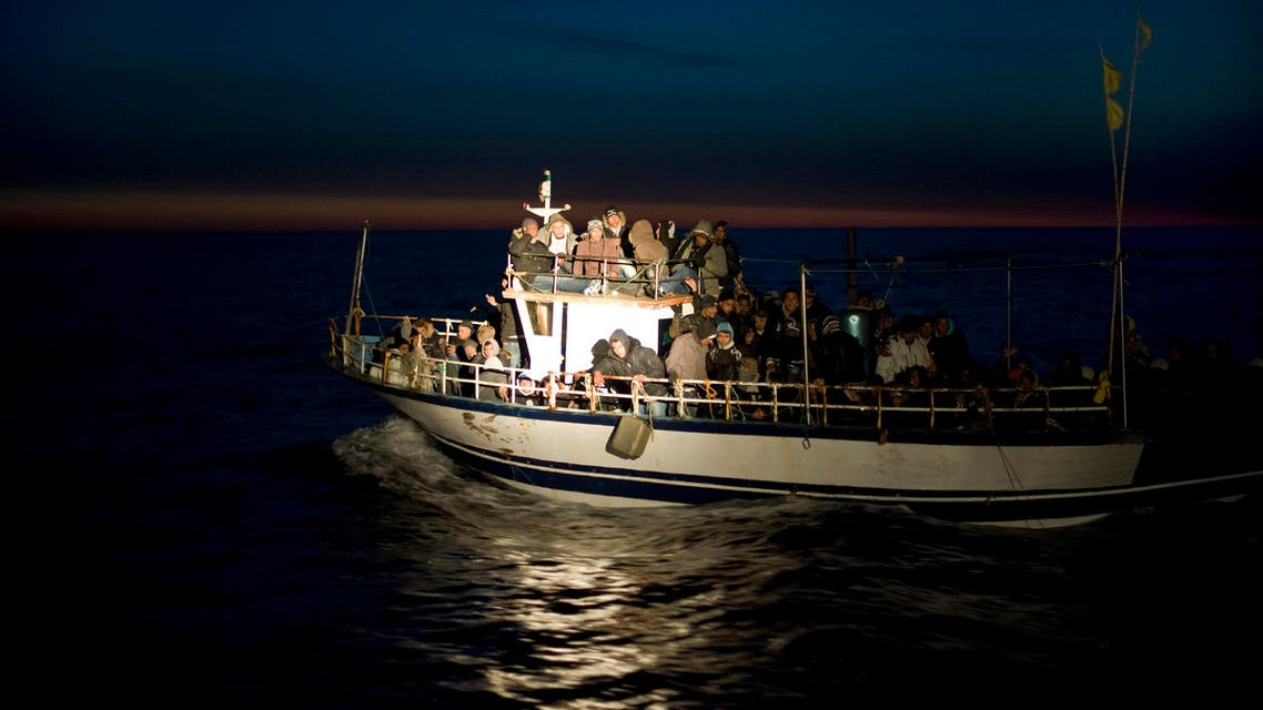 A spotlight from an Italian Coast boat shines on a boat loaded with migrants spotted at sea off the Sicilian island of Lampedusa, Italy, early Monday, March 7, 2011.