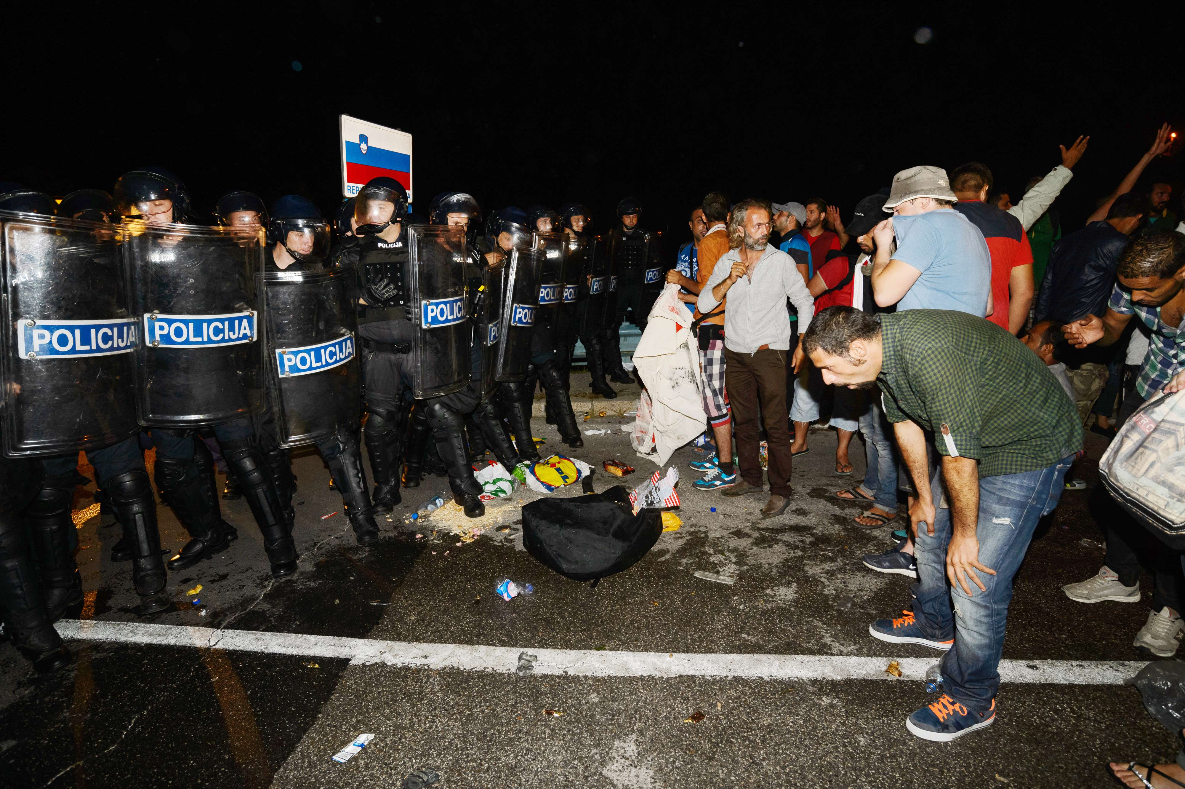 Migrants react after pepper spray was used in a small village of Rigonce in Slovenia