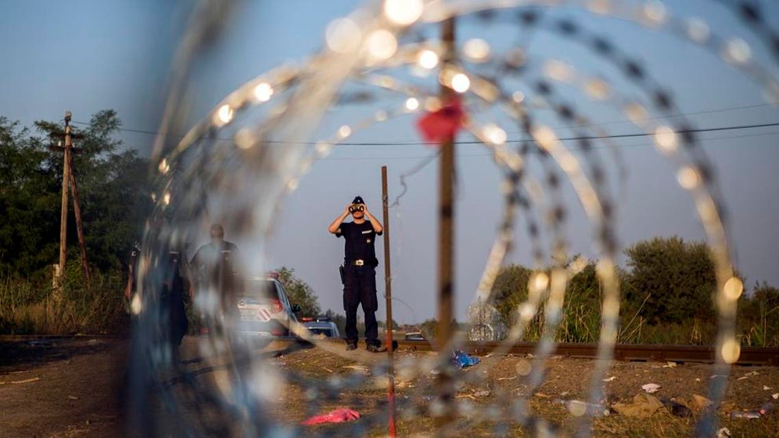 A Hungarian police officer looks through binoculars as he checks the border for refugees entering the country illegally next to the town of Röszke, Hungary. (AP Photo)