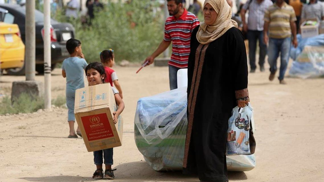 Iraqi family members internally displaced carry humanitarian aid being distributed at a refugee camp in Baghdad's western neighborhood of Ghazaliyah, Iraq, Wednesday, Sept. 16, 2015. The camp accommodating people from Anbar province's Ramadi and around received humanitarian aid Wednesday. (AP Photo/Hadi Mizban)