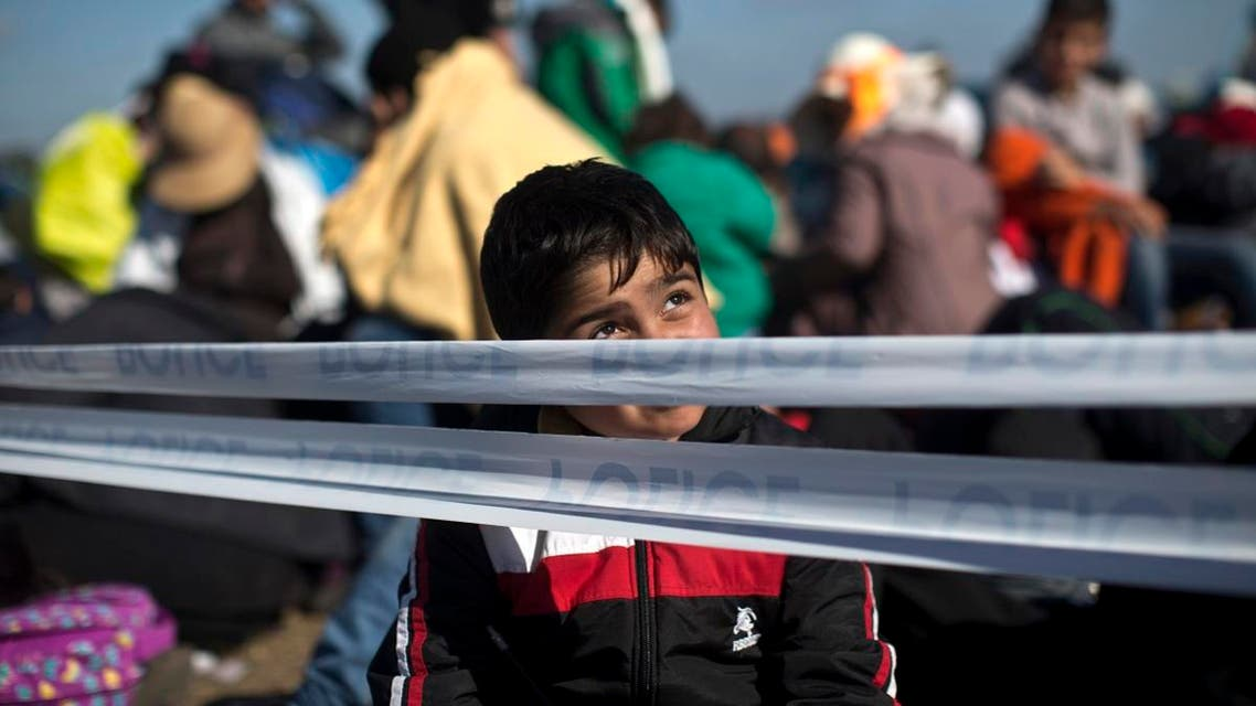 A child sits at a temporary holding camp for migrants and refugees close to Hungary's border with Serbia in Roszke, Hungary, Tuesday, Sept. 8, 2015. Hungary's prime minister Viktor Orban says he wants to speed up construction of a fence meant to stop migrants on the southern border with Serbia, a project which has missed two previous deadlines. (AP Photo/Marko Drobnjakovic)