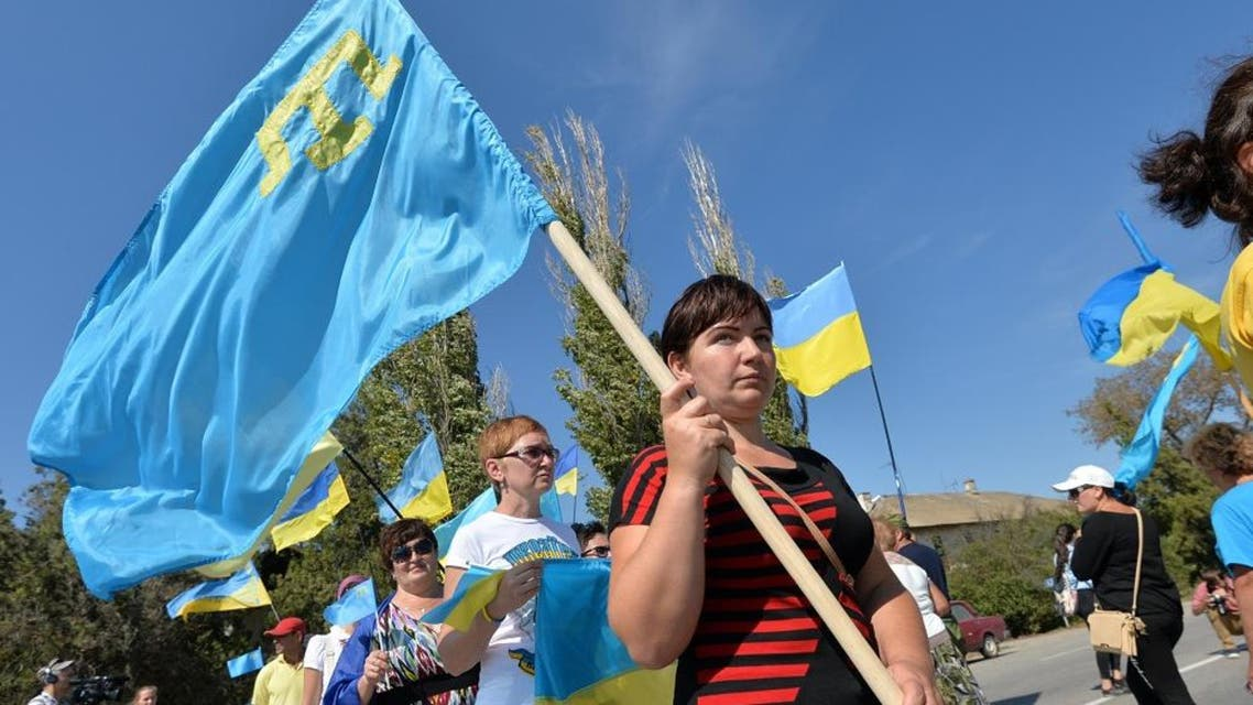 Activists hold Ukrainian and Crimean Tatar flags as they block the road at the checkpoint between Ukraine and Crimea, in Chongar, on September 20, 2015.  AP