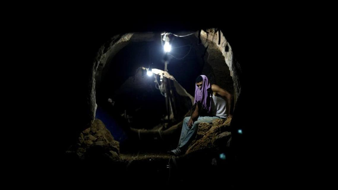 Palestinian worker rests inside a smuggling tunnel in Rafah, on the border between Egypt and the southern Gaza Strip. (File: AP)