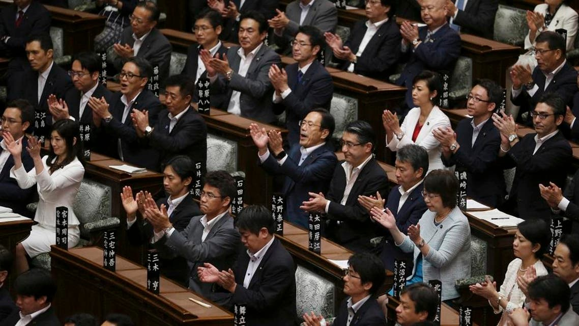 In this Saturday, Sept. 19, 2015 file photo, Japan's ruling party lawmakers applaud after contentious legislation was passed in a vote by the upper house of Parliament in Tokyo. In the wee hours of Saturday morning, Japan took a step toward having a military in line with most armed forces around the world, one that would be able to take part in combat even when the country is not under direct attack. While Japan's military remains far from unfettered, the package of bills approved by parliament is a further step in a gradual erosion of the restrictions that has been underway for more than two decades. (AP Photo/Koji Sasahara, File)