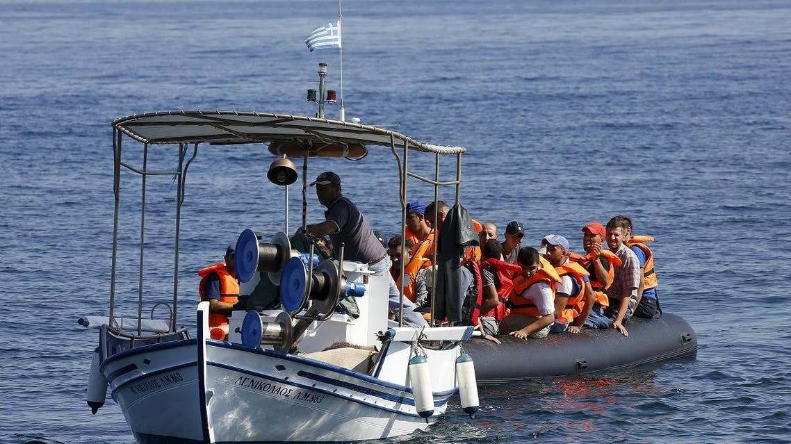 A Greek fisherman tows a dinghy overcrowded with Syrian refugees after its engine broke off the Greek island of Lesbos while crossing a part of the Aegean Sea from the Turkish coast September 19, 2015. REUTERS/Yannis Behrakis