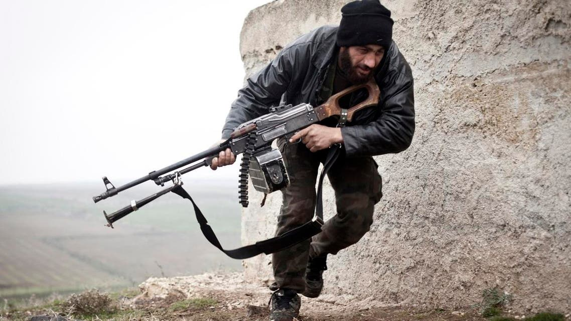 In this December 17, 2012, file photo, a Free Syrian Army fighter takes cover during fighting with the Syrian Army in Azaz, Syria. Syrian rebels on Friday, May 8, 2015, voiced serious reservations about a U.S. program to train moderate rebels which U.S. and Jordanian officials say has kicked off in Jordan, dismissing it as a drop in the ocean that would not change realities on the ground. (AP Photo/Virginie Nguyen Huang, File)