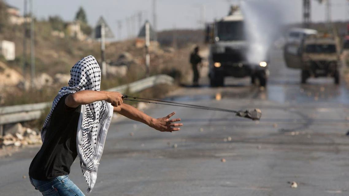 A Palestinian uses a sling shot to throw stones towards Israeli AP
