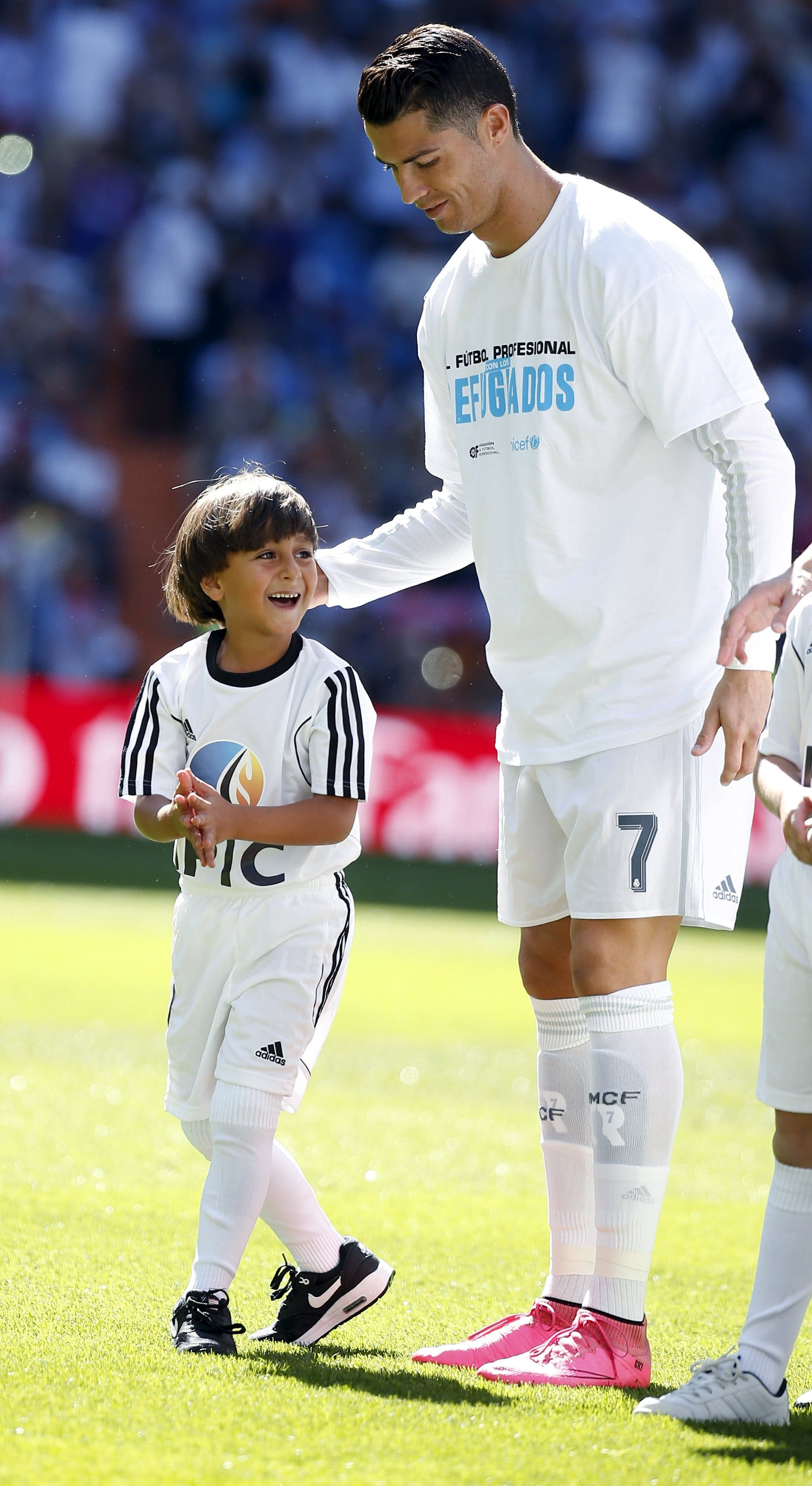 Zaid, 7, son of Osama Abdul Mohsen, a Syrian refugee who was filmed being tripped by a camerawoman as he fled police in Hungary with him, smiles as he stands next to Real Madrid's Cristiano Ronaldo before the Spanish first division soccer match against Granada at Santiago Bernabeu stadium in Madrid, Spain, September 19, 2015. REUTERS/Sergio Perez
