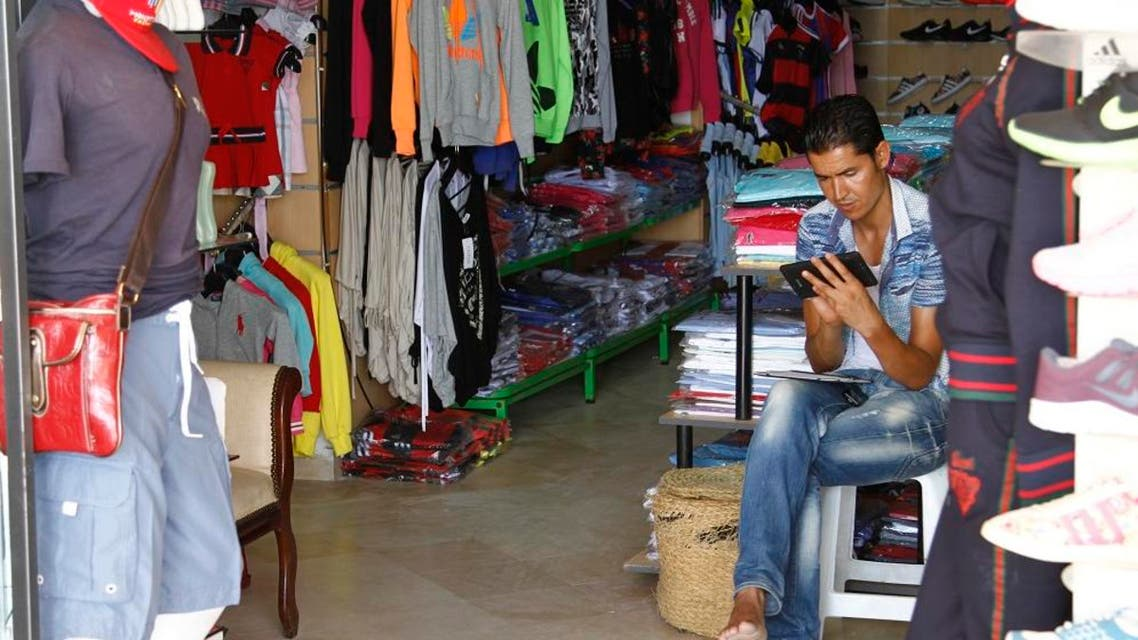 In this photo taken on Aug. 9, 2015, a tourist shop worker plays a game on his phone in the absence of any customers in Hammamet, Tunisia. AP