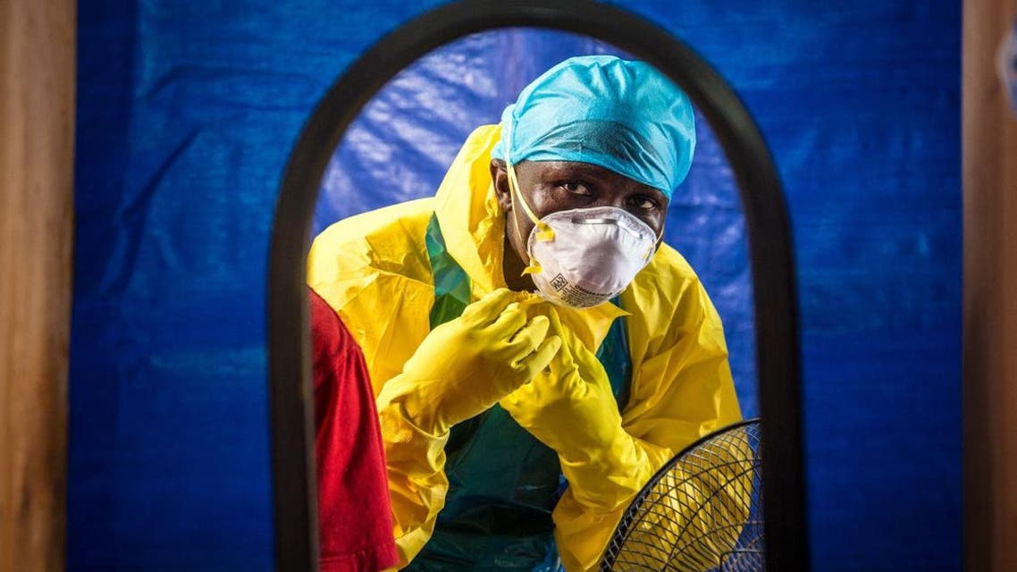 In this Oct. 16, 2014, file photo, a healthcare worker dons protective gear before entering an Ebola treatment center in Freetown, Sierra Leone.