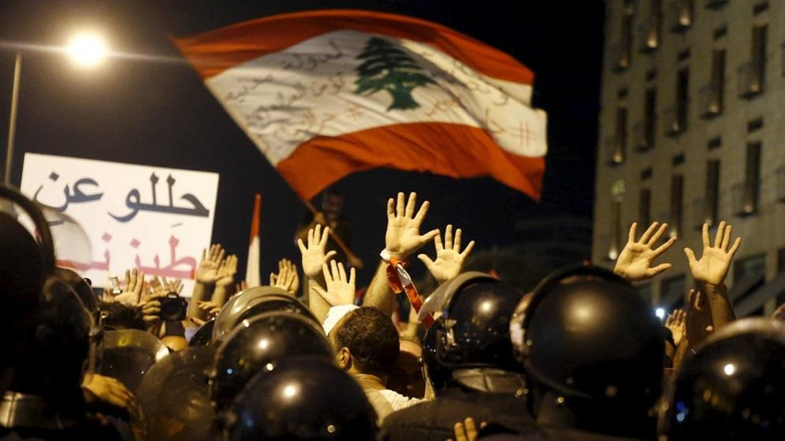 Protesters raise their hands facing riot police during a protest against perceived government failures, including a rubbish disposal crisis, in downtown Beirut. (Reuters)
