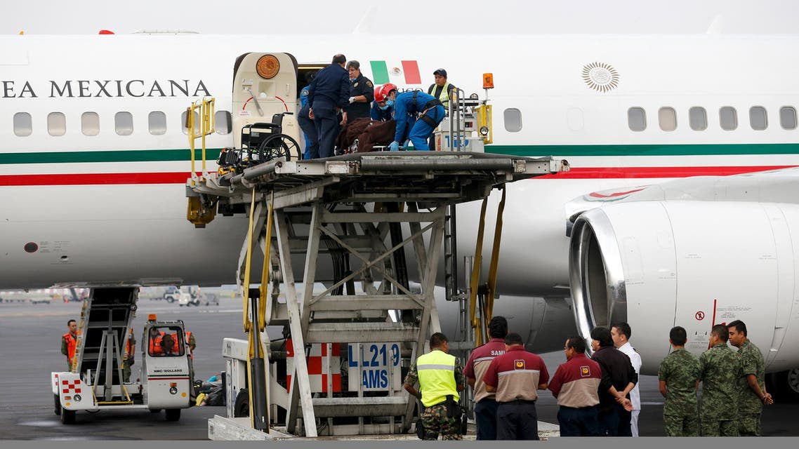 Paramedics (top) carry the stretcher of a Mexican tourist, who was injured during an attack in Egypt, to a platform from a plane, after their arrival to the presidential hangar in Mexico City, September 18, 2015. Six Mexican tourists who survived a deadly air raid on their convoy by Egyptian security forces returned home on Friday, as the government vowed to press for answers over how the group was mistaken for militants. Wrapped in blankets, some draped with red, white and green Mexican flags and strapped to gurneys, survivors were lowered on a platform from the presidential plane, which President Enrique Nieto sent to Egypt with the foreign minister to bring them home. REUTERS/Tomas Bravo