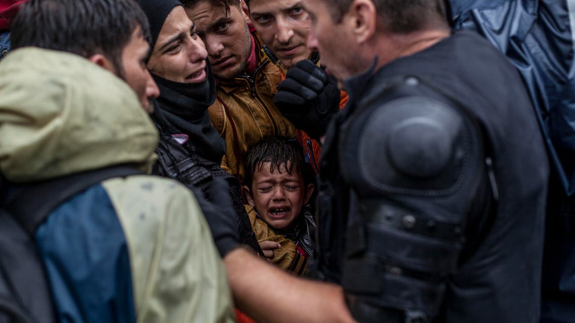 A Syrian refugee boy cries while he and his family try to board a train at the station in Tovarnik, Croatia, Sunday, Sept. 20, 2015. Police said Saturday more people are coming in from Serbia, mostly near the eastern border town of Tovarnik, where there are already around 2,500 people waiting for transport. (AP Photo/Manu Brabo)