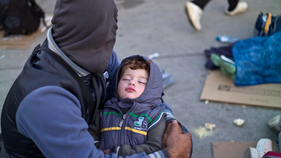 A Syrian refugee man holding his sleeping son, rests on the ground after spending the night at a collection point in the truck parking lot of the former border station on the Austrian side of the Hungarian-Austrian border near Nickelsdorf, Austria, Wednesday, Sept. 23, 2015. AP