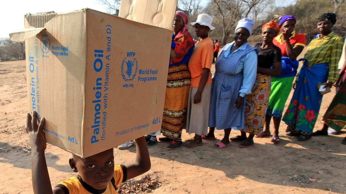 A young boy carries a box with items distributed by the United Nations World Food Programme (WFP) in Mwenezi, about 450 kilometers (280 miles) south of Harare, Zimbabwe, Wednesday, Sept. 9 2015. According to the United Nations and the Zimbabwean government some about 1.5 million people face severe food shortages due to a consecutive bad harvests and poor rains. (AP Photo/Tsvangirayi Mukwazhi)
