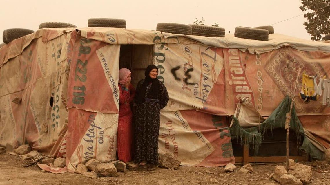Syrian refugees stand outside their tents during a sandstorm in a refugee camp in the town of Bar Elias, in Lebanon's Bekaa Valley, on Sept. 8, 2015. (AP Photo/Bilal Hussein)