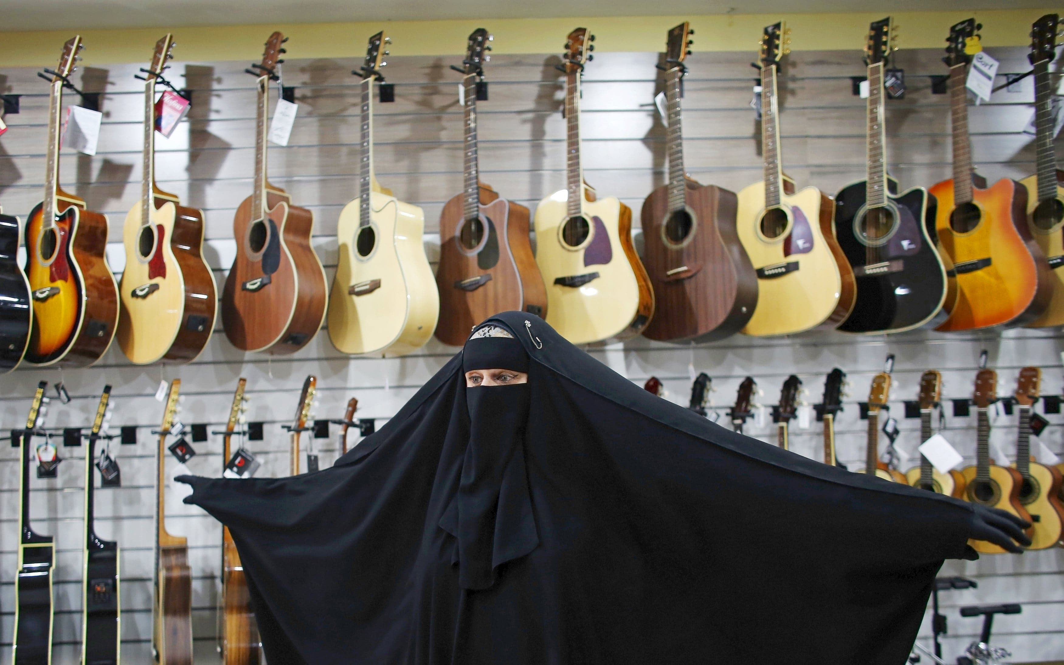 Gisele Marie, a Muslim woman and professional heavy metal musician, gestures in front of a wall of guitars, at a shop selling musical instruments in Sao Paulo August 13, 2015. (Reuters)