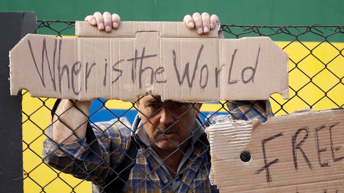 A man holds onto a fence outside a train that was stopped in Bicske, Hungary, Friday, Sept. 4, 2015. (AP)