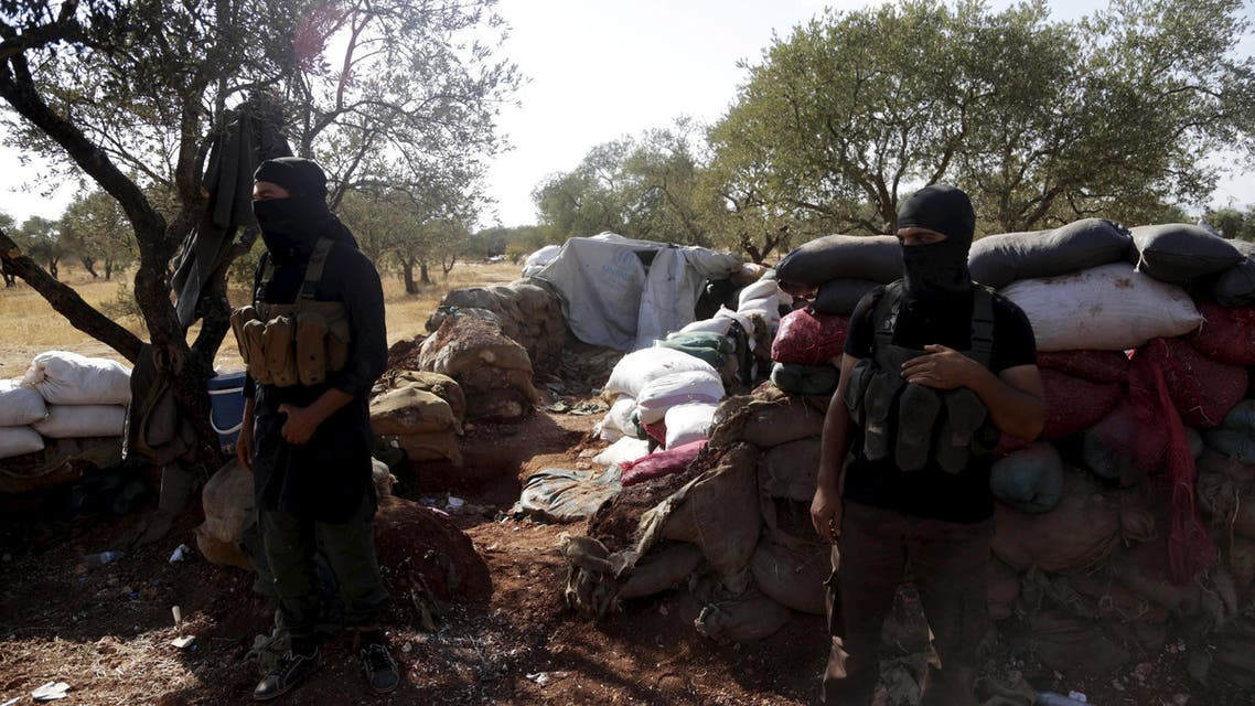 Members of al Qaeda's Nusra Front stand in front of piled sandbags near the two Shi'ite Muslim towns of al-Foua and Kefraya in northwestern Syria, September 22, 2015. Warring parties have agreed to extend ceasefires in two Shi'ite Muslim towns in northwestern Syria and another settlement near the Lebanese border until a wider deal is reached, the al-Manar TV station controlled by Lebanon's Hezbollah said on Tuesday. Pro-government militia backed by Shi'ite Hezbollah have been defending the two towns - al-Foua and Kefraya - against insurgent attacks. REUTERS/Khalil Ashawi