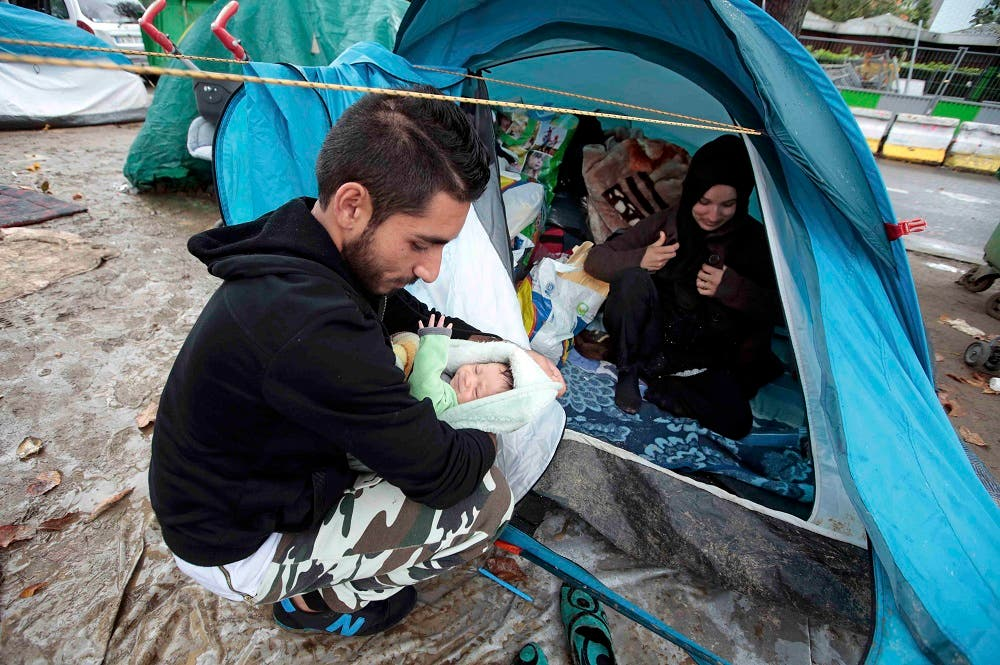 Ehab Ali Naser, a 23 year-old Syrian refugee, holds a 12 day-old baby at a makeshift camp on a street, northern Paris, France, September 16, 2015. Ehab, in Paris for a month, arrived after an 18-month journey that started in his hometown of Homs, Syria, where he was a vendor at the souk. He spent a year in Lebanon, then travelled to Algeria and Morocco before he arrived in the Spanish port of Melila, and then headed to France. Currently he lives in a tent in a small refugee camp along a busy boulevard on the outskirts of Paris. Ehab has always dreamt of becoming a singer and one day his path crosses with that of a French producer, writer and composer visiting the refugee camp at Porte de Saint Ouen, who gives him the chance to try out his voice in a professional music studio. Picture taken September 16, 2015. REUTERS/Eric Gaillard