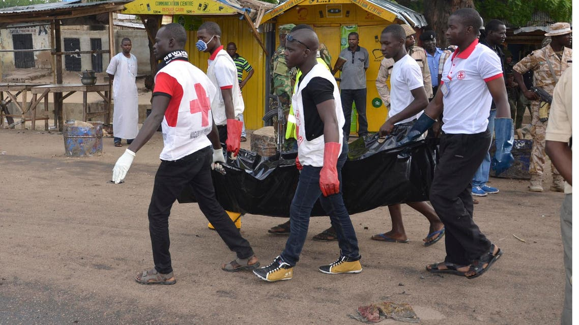 Red cross officials carry a body at the site of a bomb explosion in Maiduguri, Nigeria, Friday, July 31, 2015 . A woman suicide bomber killed many people at a crowded market early Friday in a blast that thundered across the northeastern Nigerian city of Maiduguri, witnesses said. (AP Photo/Jossy Ola)