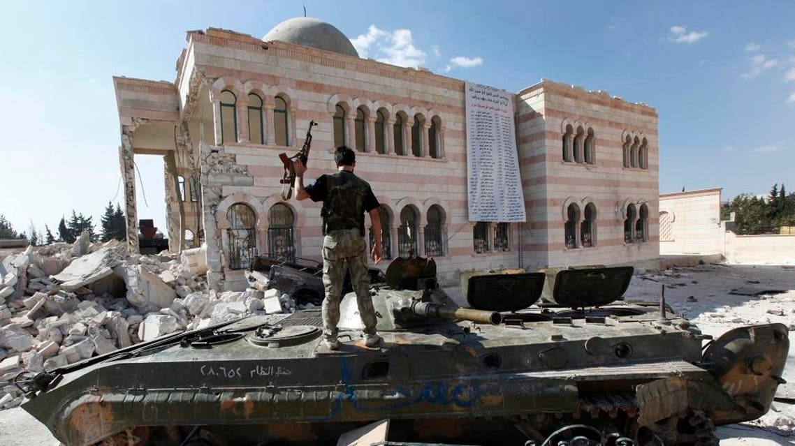 File photo of a Free Syrian Army soldier standing on a damaged Syrian military tank in front of a damaged mosque, which were destroyed during fighting with government forces. (File photo: AP)