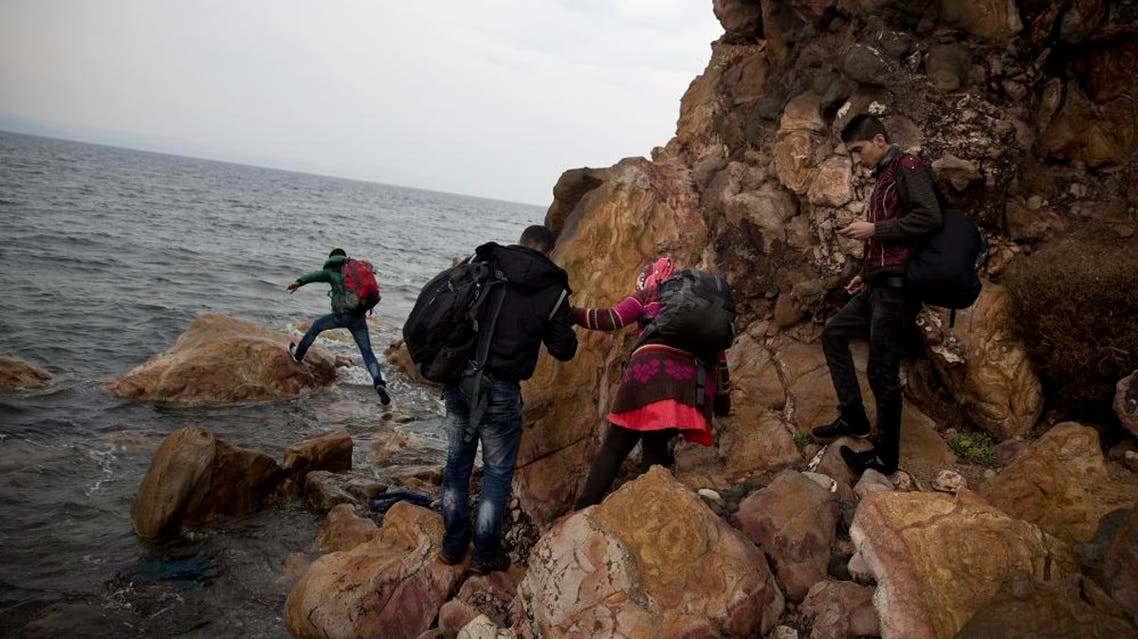 Syrian refugees who arrived on the shores of the Greek island of Lesbos after crossing the Aegean Sea from Turkey on a inflatable dinghy, clamber over rocks on Tuesday, Sept. 22, 2015.