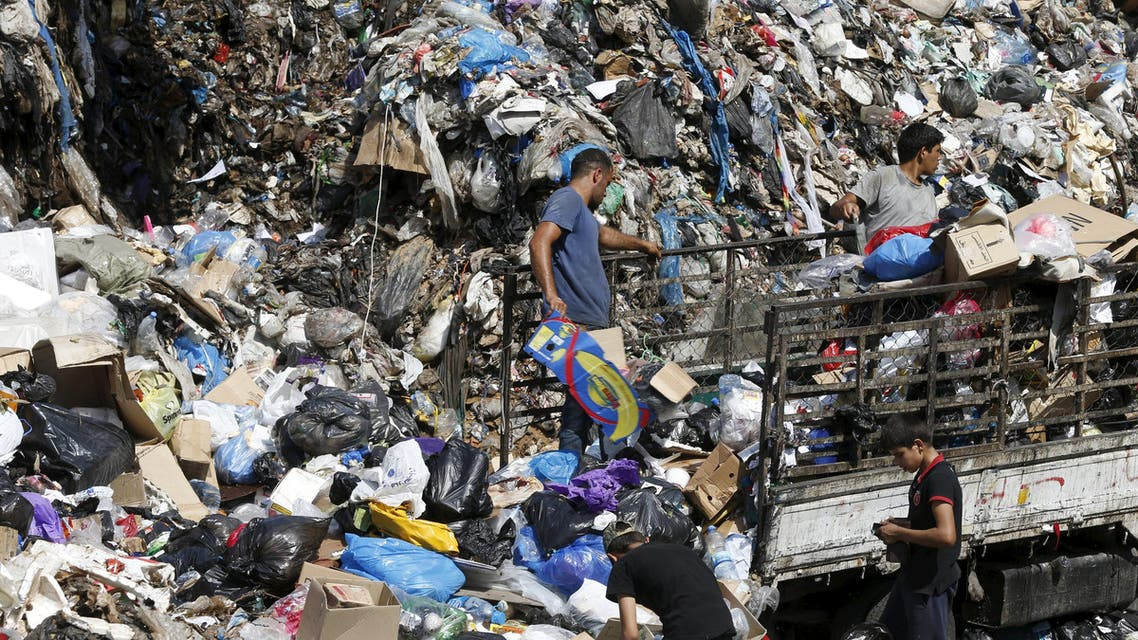 Men unload trash from a pick-up truck as scavengers sift through garbage at a temporary dump on the edge of Beirut river, Lebanon September 23, 2015. Lebanon has been hit by a series of protests over a trash crisis that has led to piles of refuse building up in the streets in recent weeks, as well as anger about political paralysis. REUTERS/Mohamed Azakir