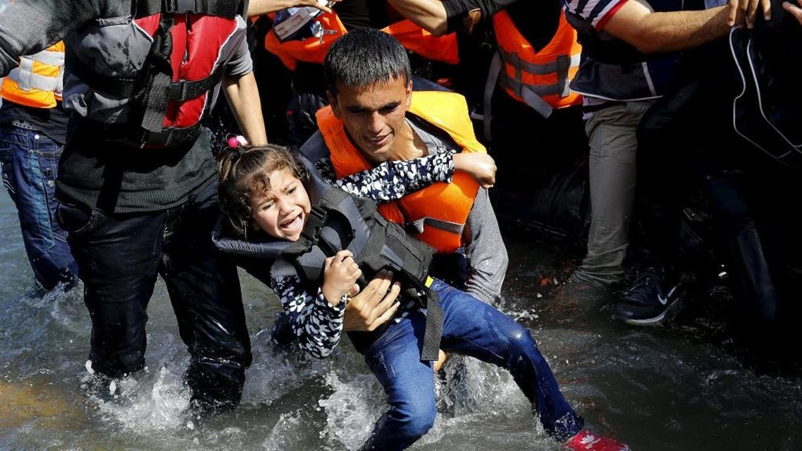 A Syrian refugee man struggles to carry his daughter off a dinghy at a beach after arriving on the Greek island of Lesbos, after crossing a part of the Aegean Sea from Turkey to Lesbos, September 25, 2015. REUTERS/Yannis Behrakis