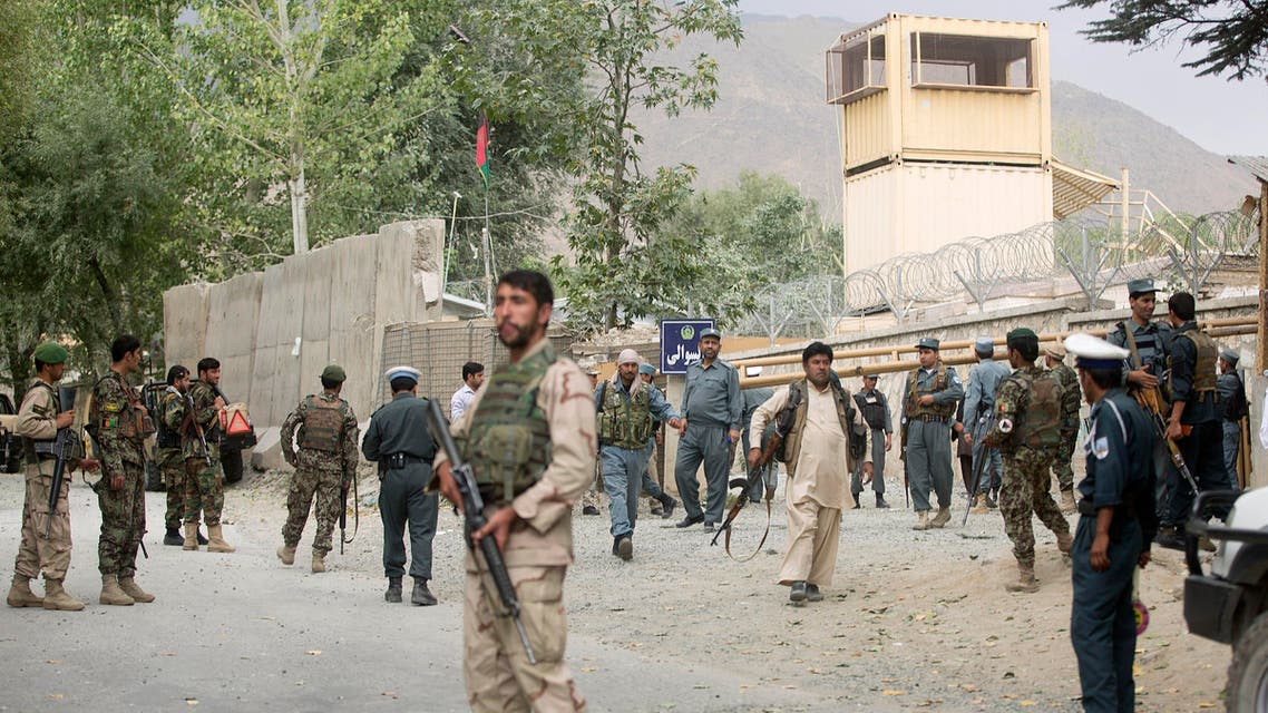 Afghan security forces gather near the main gate of Paghman district governor's compound where a suicide car bomb attack happened in Paghman district of Kabul province, Afghanistan, Wednesday, Sept. 16, 2015. The attack killed four people, including the local chief of criminal investigations, in the Paghman district, west of the capital Kabul. (AP Photo/Ahmad Nazar)