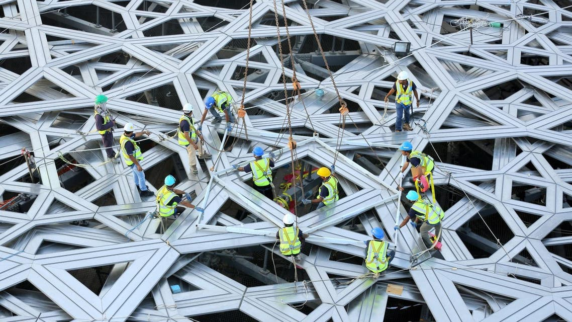 017 - Saadiyat Island, -, UNITED ARAB EMIRATES : A handout image from Abu Dhabi Tourism Development & Investment Company (TDIC) made available on September 27, 2015 by the United Arab Emirates News Agency (WAM) shows workers placing the final piece of the outer cladding of the dome structure of the future Louvre museum still under contruction on Saadiyat island, near Abu Dhabi. The museum is expected to open by the end of 2016. AFP PHOTO / HO / WAM
