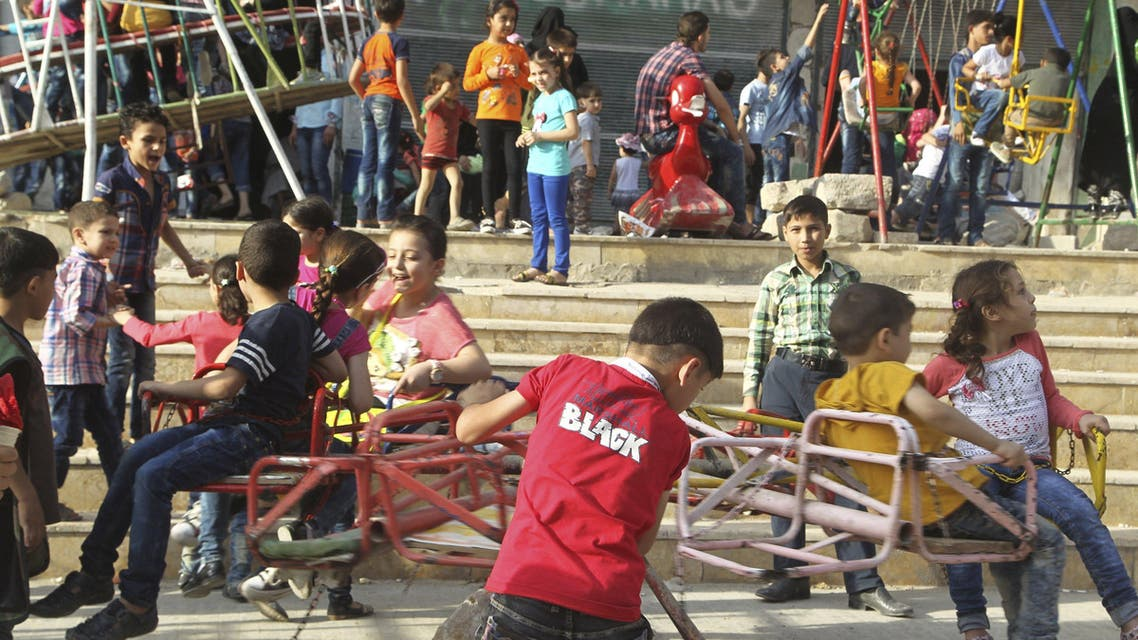 Children play on fairground rides during Eid celebrations in Al-Fardous neighbourhood of Aleppo, Syria September 27, 2015. Muslims across the world are celebrating the annual festival of Eid al-Adha or the Feast of the Sacrifice, which marks the end of the annual haj pilgrimage, by slaughtering goats, sheep, cows and camels in commemoration of Prophet Abraham's readiness to sacrifice his son to show obedience to Allah. REUTERS/Abdalrhman Ismail