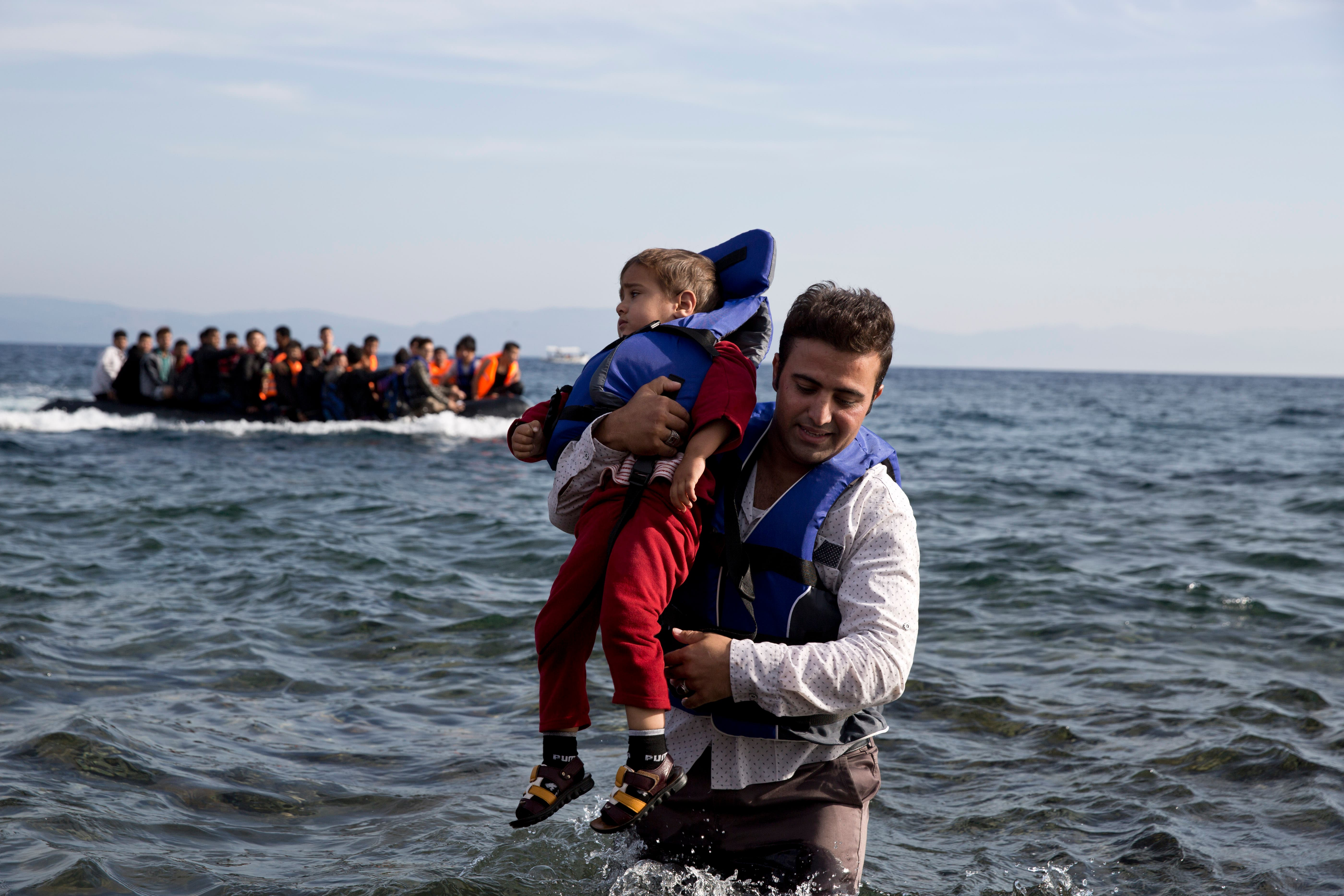 A Syrian refugee carries his child after they arrived from Turkey to the shores of the Greek island of Lesbos, on an inflatable dinghy, with another boat in the background, Saturday Sept. 26, 2015. More than 260,000 asylum-seekers have arrived in Greece so far this year, most reaching the country's eastern islands on flimsy rafts or boats from the nearby Turkish coast. (AP Photo/Petros Giannakouris)