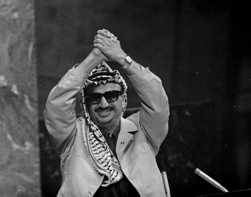 In this Nov. 13, 1974 file photo, Palestine Liberation Organization leader Yasser Arafat clasps his arms over his head as he addresses the United Nations General Assembly. 'I have come bearing an olive branch and a freedom fighter's gun,' he said. 'Do not let the olive branch fall from my hands.'